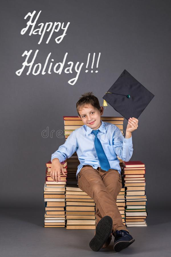The boy is leader, sitting in the throne from books, greets the audience with mortarboard stock image