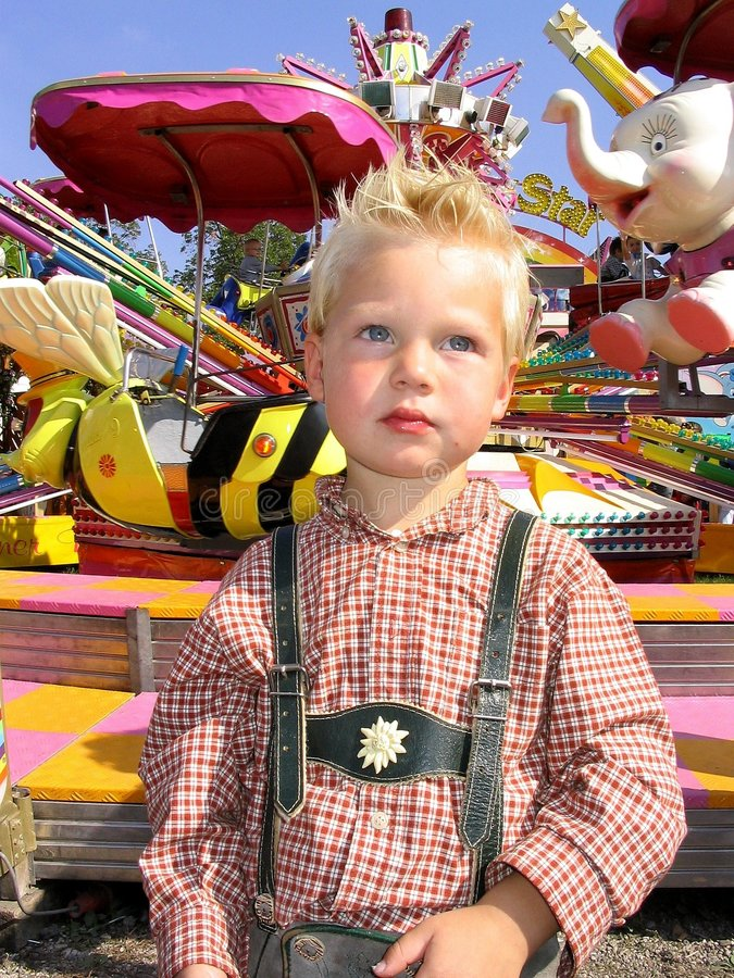 Boy in leaderhosen. Boy in lederhosen at funfair stock images