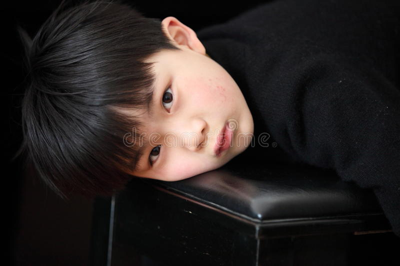 The boy in the black. A boy leaning on a black stool royalty free stock photo
