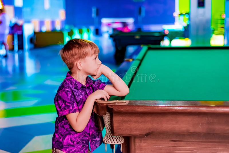 The boy is leaning on a pool table and waiting with someone to play table billiards stock photos