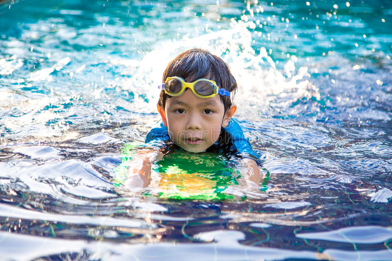 Boy learn to swim in the swimming pool stock image