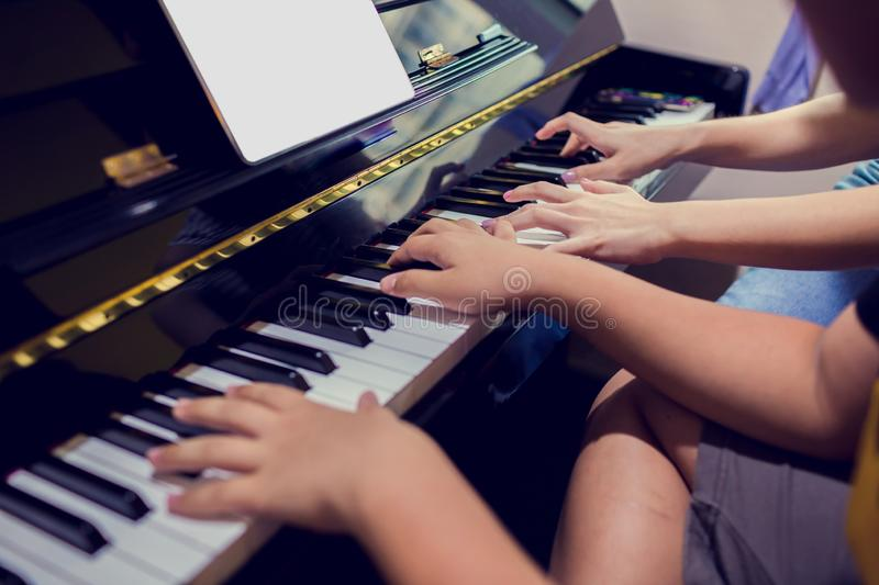 A boy is learning piano with woman teacher and music notation on tablet, four hands from two people playing piano stock image