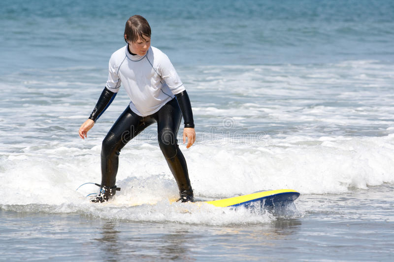 Boy learning to surf 2. A boy in a wet suit learning to surf. This photo is taken on Borth beach in the west of Wales stock images