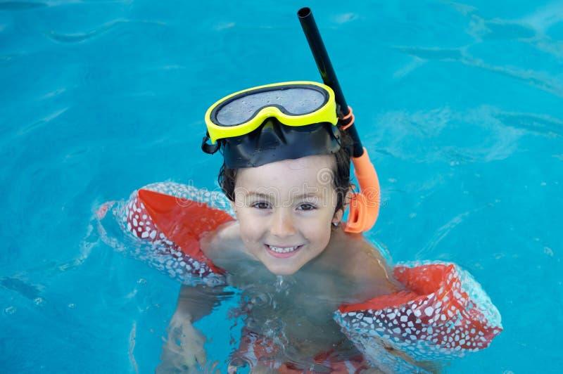 Boy learning to swim stock photo