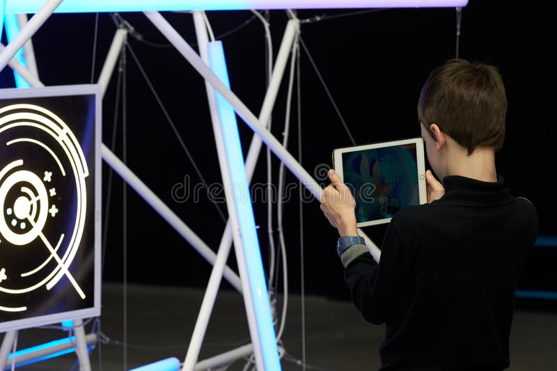 A boy learns the basics of designing and modeling robots. Rostov-on-Don, RUSSIA - January 5, 2019: A boy learns the basics of designing and modeling robots using royalty free stock image