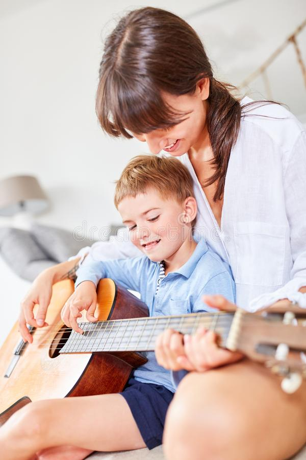Boy learns first grips on the guitar stock photo