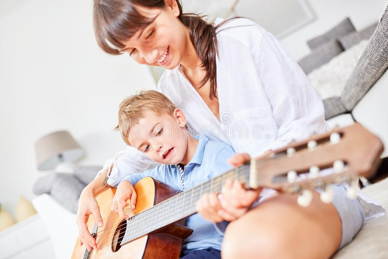 Boy learns to play guitar at home royalty free stock photo