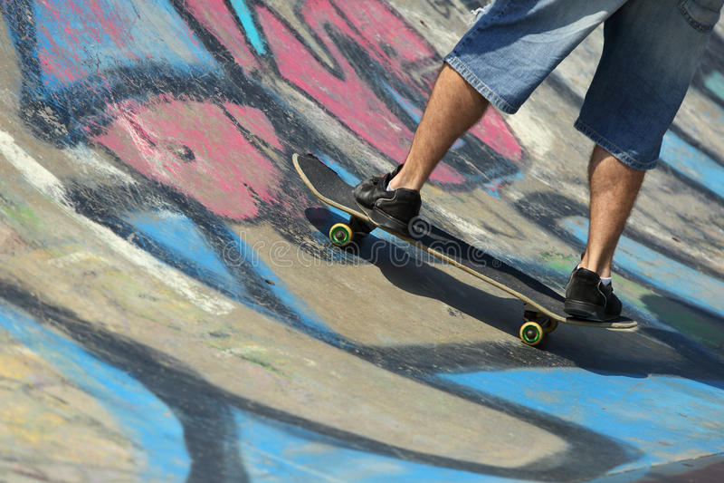 Boy legs on a skateboard royalty free stock image