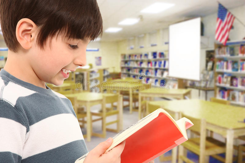 Boy in Library Reading Book. Happy attractive 7 year old boy in school library reading book smiling royalty free stock photography