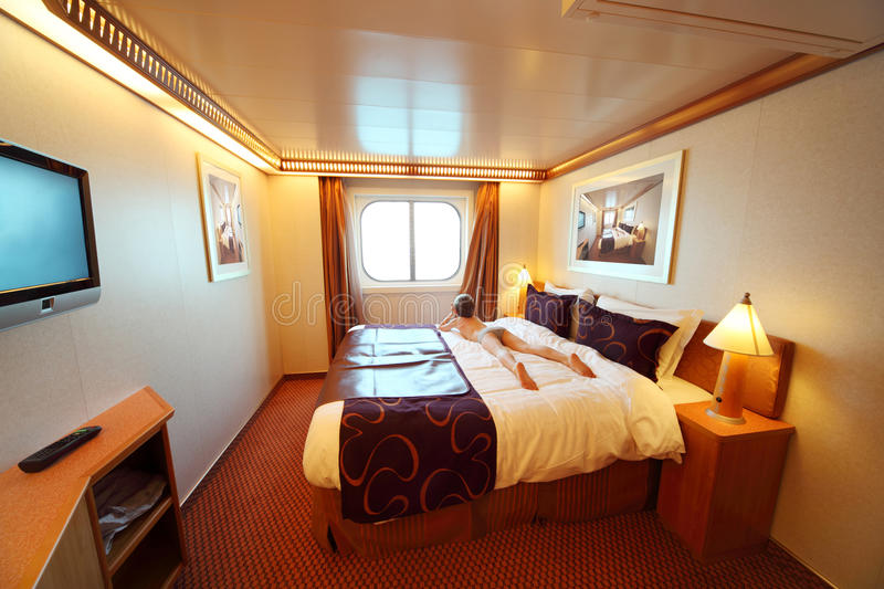 Boy lies on bed in ship cabin general view stock photo