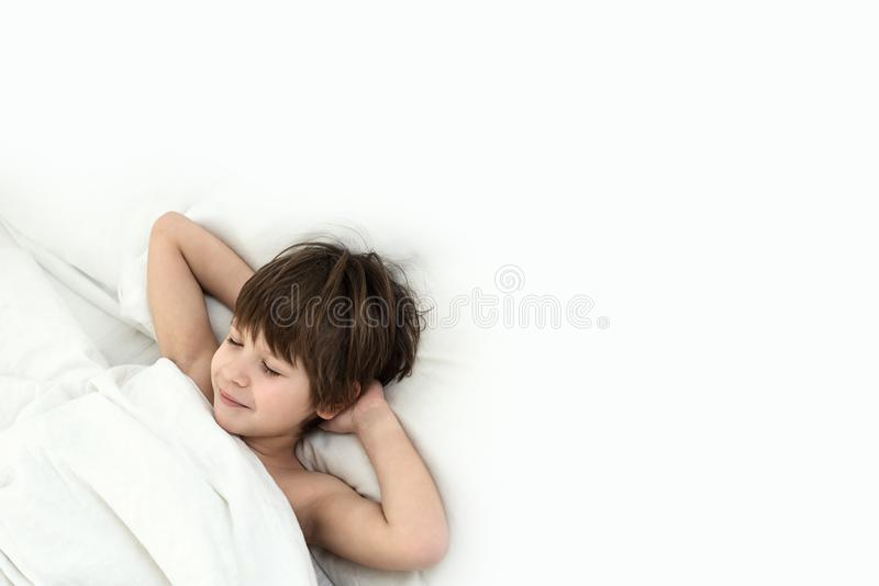 Boy lies in a bed on a white bedclothes. slipping child. Slipping boy 6 years with a lies in a bed on a white bedclothes royalty free stock image