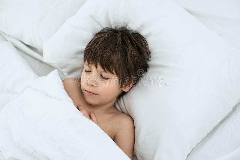 Boy lies in a bed on a white bedclothes. slipping child. Slipping boy 6 years with a lies in a bed on a white bedclothes stock images