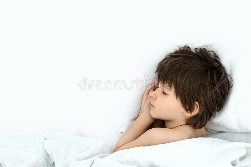 Boy lies in a bed on a white bedclothes. slipping child. Slipping boy 6 years with a lies in a bed on a white bedclothes stock photo