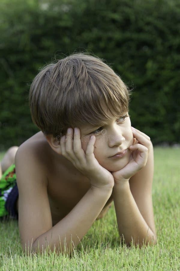 The Boy Lies On A Lawn Stock Photos