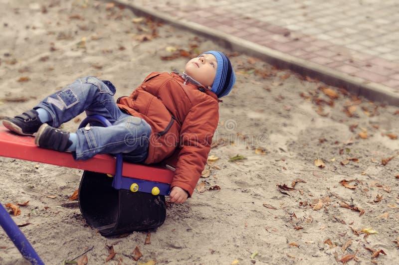 Boy lies on a swing upside down stock photos