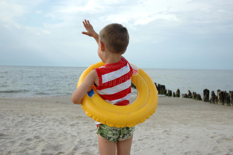 Boy with lifebelt. Young boy is standing on the beach with lifebelt royalty free stock images