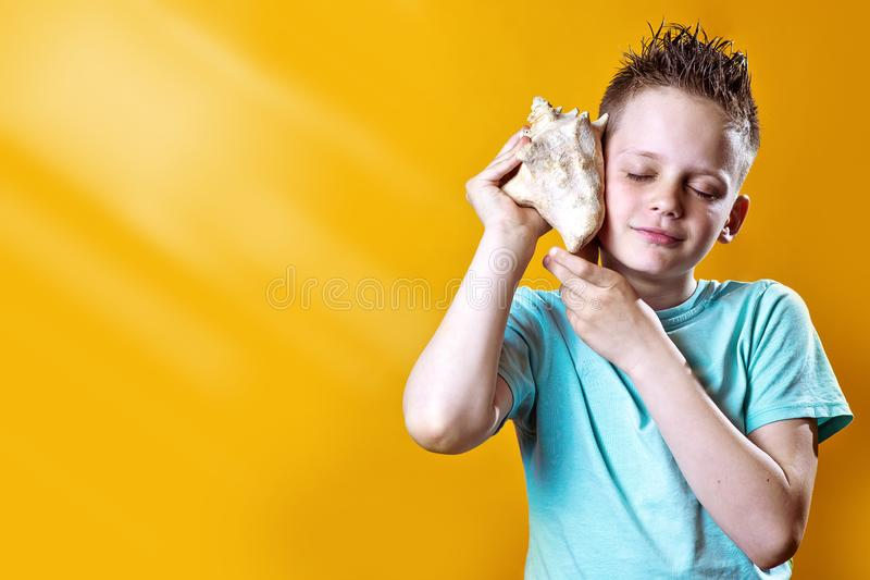 A boy in a light t-shirt listens to the sea in a sea shell on a colored background. A boy in a light t-shirt listens to the sea in a sea shell on a bright royalty free stock photos
