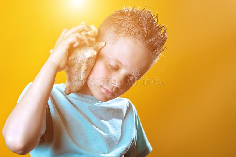 A boy in a light t-shirt listens to the sea in a sea shell on a colored background. A boy in a light t-shirt listens to the sea in a sea shell on a bright royalty free stock image