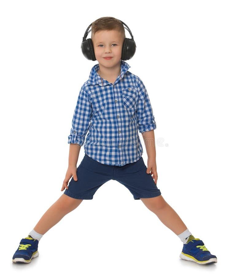 Boy listening music in headphones stock photography