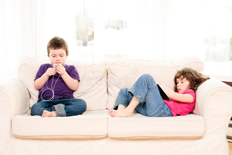 Children chilling on a couch. Boy listening to music and girl reading on a couch stock photography