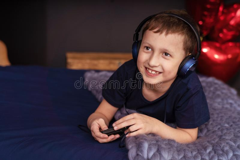 Boy listening to music in headphones Lying in bed. The boy listens to music with headphones lying in bed. portrait of a smiling child in headphones royalty free stock image