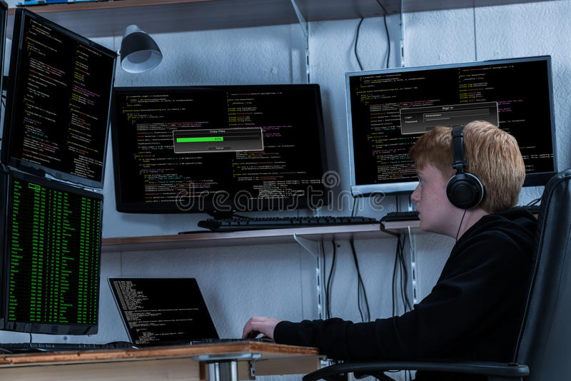 Boy Stealing Data From Multiple Computers. Boy Listening To Music While Stealing Data From Multiple Computers stock photography