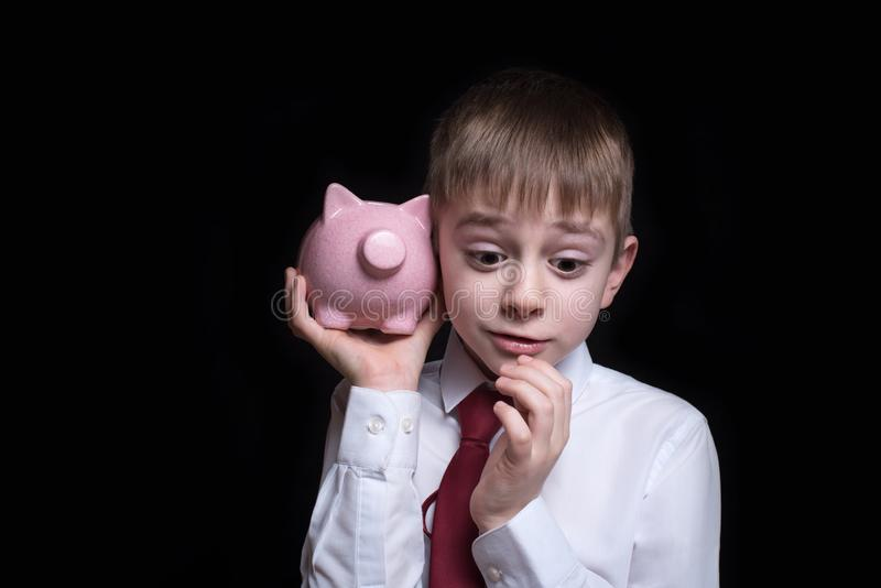 Boy listens attentively to the pink piggy bank. Business concept. Black background.  stock image
