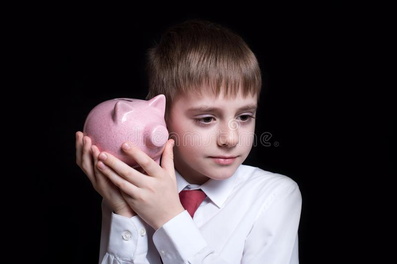 Boy listens attentively to the pink piggy bank. Business concept. Black background.  royalty free stock image