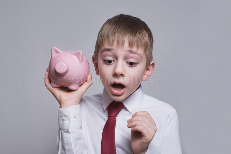 Boy listens attentively to the pink piggy bank. Business concept. Light background.  stock photo