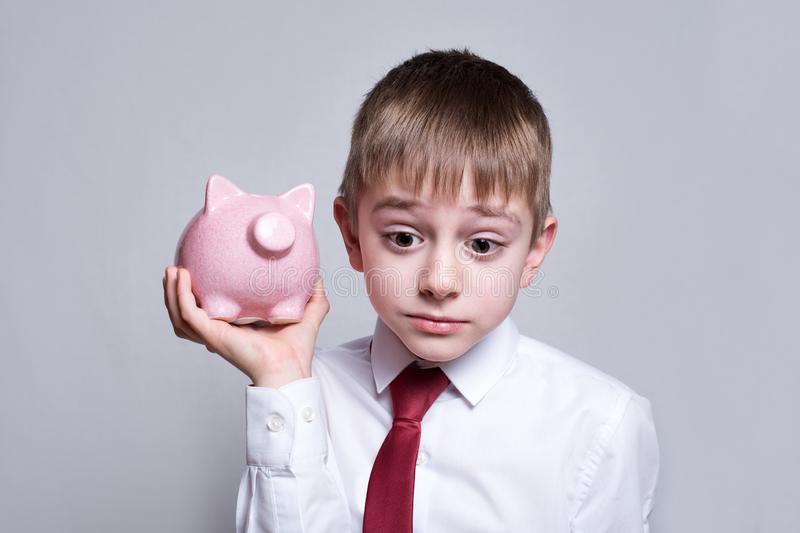 Boy listens attentively to the pink piggy bank. Business concept. Light background.  royalty free stock image