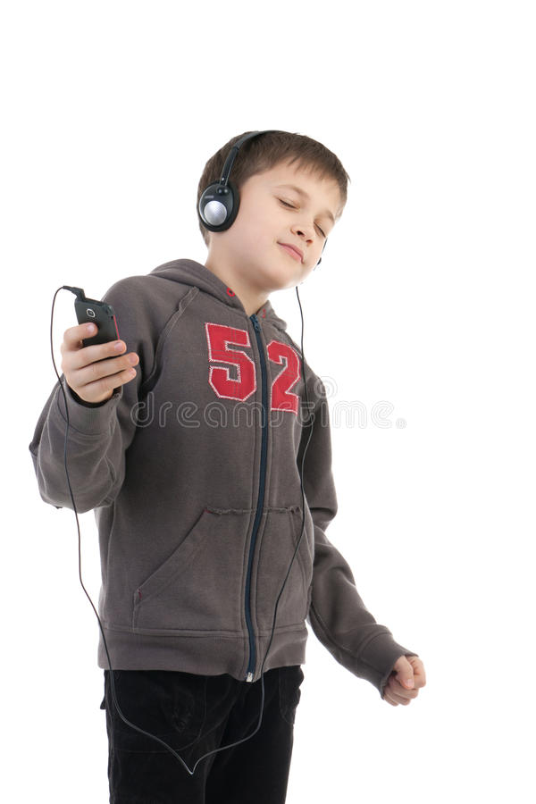 The boy listens to music. The boy in ear-phones listens to music stock photo