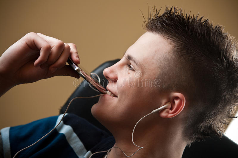 Boy listens to music. Happy teenage boy listens to music on his portable mp3 player stock photo