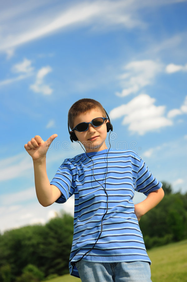 Boy listens to music. Young boy wearing headphones listens to music royalty free stock photo