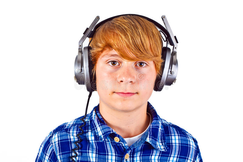 Boy listens to music with his headphones. Teenage boy listens to music with his headphone stock image
