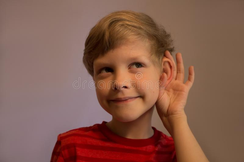 The boy listens very attentively. He listens very attentively. He pushes his ear and listens. His face is smiled stock photos