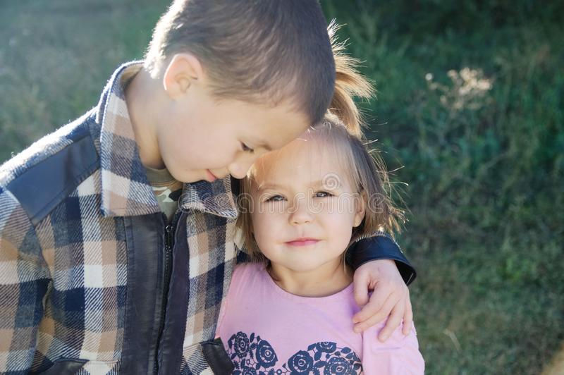 Boy and little girl hugging portrait. Happy smiling children outdoors at sunny day.Friendship siblings. Brother embrace sister stock images