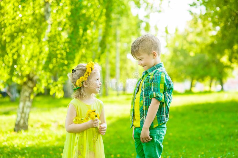 Boy with little girl in the park summer day stock image