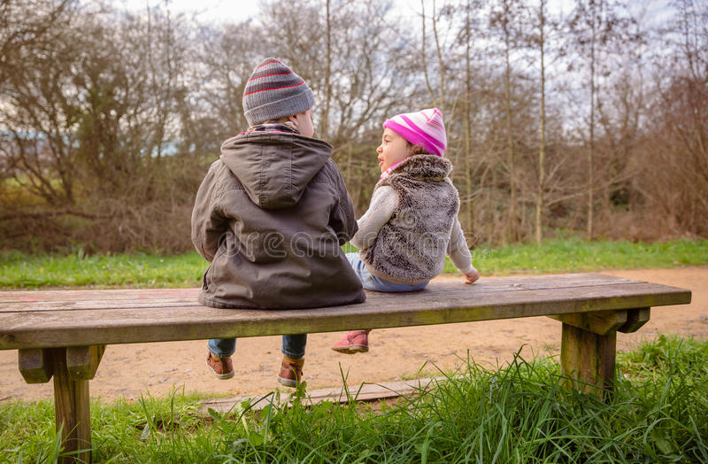 Boy and little girl talking sitting on a bench royalty free stock photo