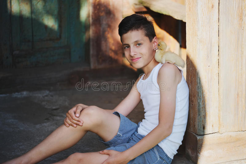 Boy with little yellow duckling in summer village royalty free stock photo
