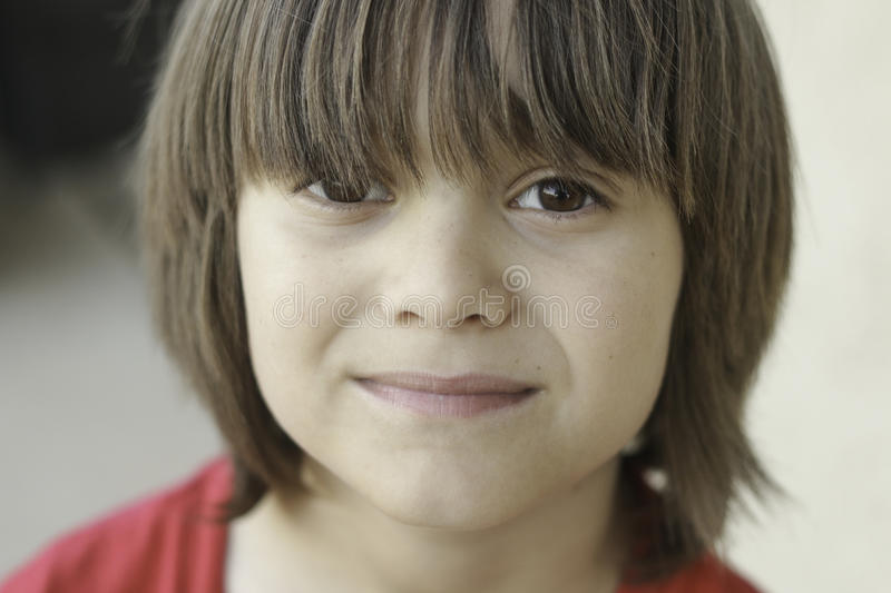 Boy with long bangs. A closeup portrait of a boy with brown eyes and long bangs looking straight at the camera royalty free stock photography