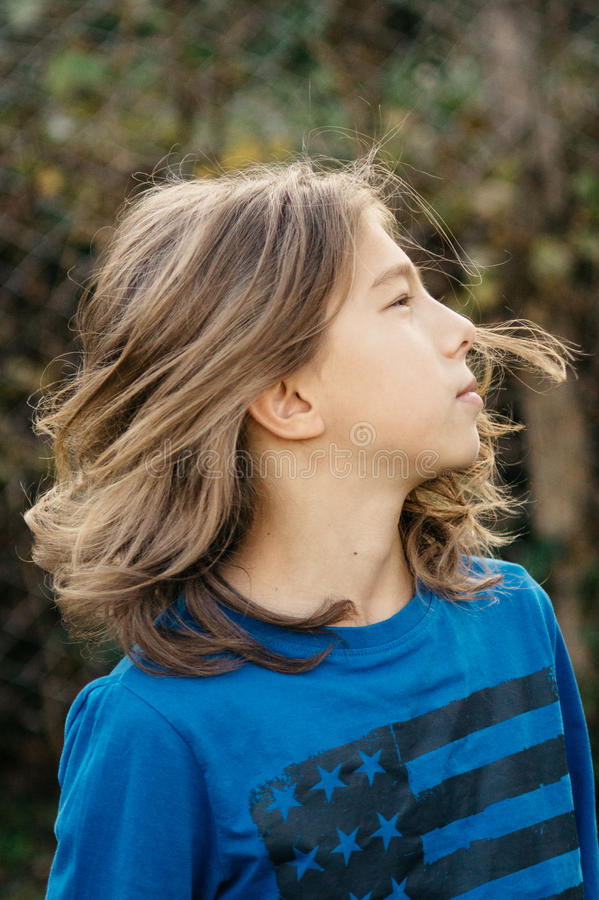Boy with long hair. Teen boy with beautiful long hair royalty free stock image