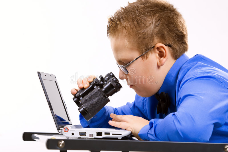 Boy looking at computer screen in binoculars royalty free stock photo
