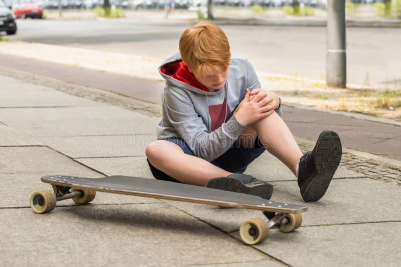 Boy Looking At His Injured Leg royalty free stock images