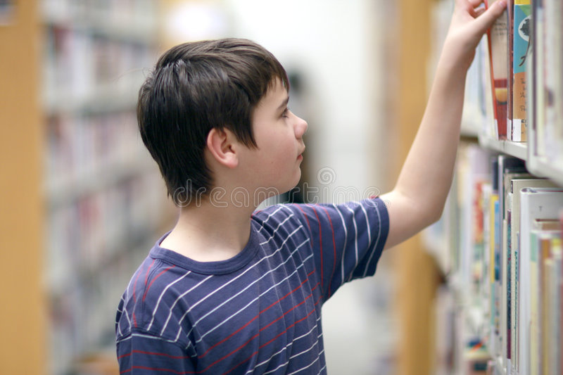 Boy looking for library book. Boy in the library looking for the book stock images