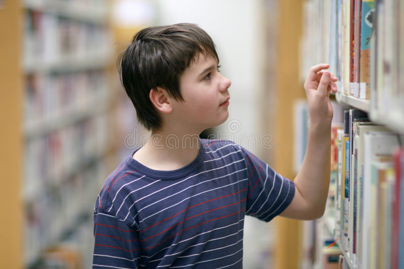 Boy looking for library book. Boy in the library looking for the book royalty free stock photography
