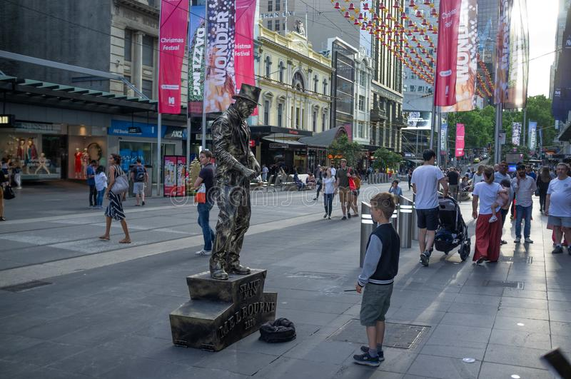 Boy looking at living statue performer bronze man. stock image