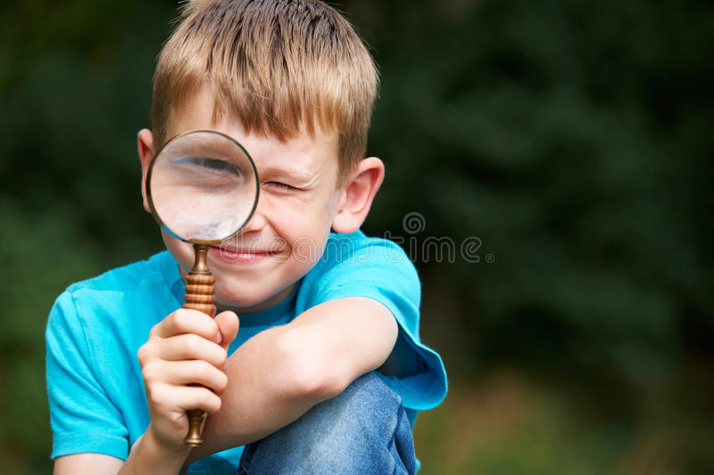 Boy Looking Through Magnifying Glass With Magnified Eye. Boy Looks Through Magnifying Glass With Magnified Eye royalty free stock photography