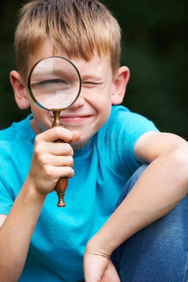 Boy Looking Through Magnifying Glass With Magnified Eye. Boy Looks Through Magnifying Glass With Magnified Eye royalty free stock images