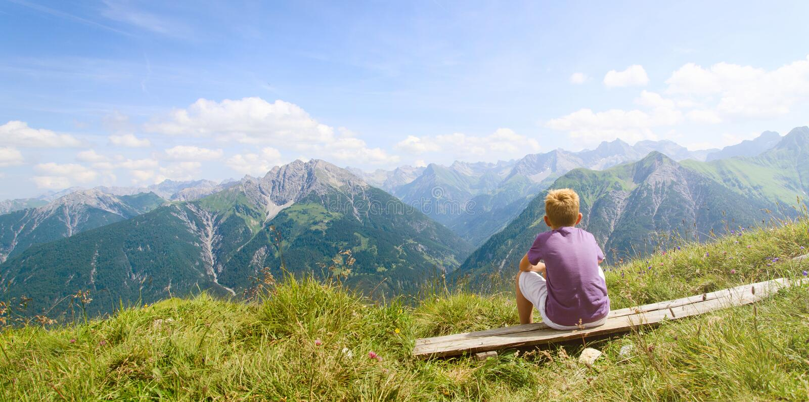 Boy looking at mountains stock image
