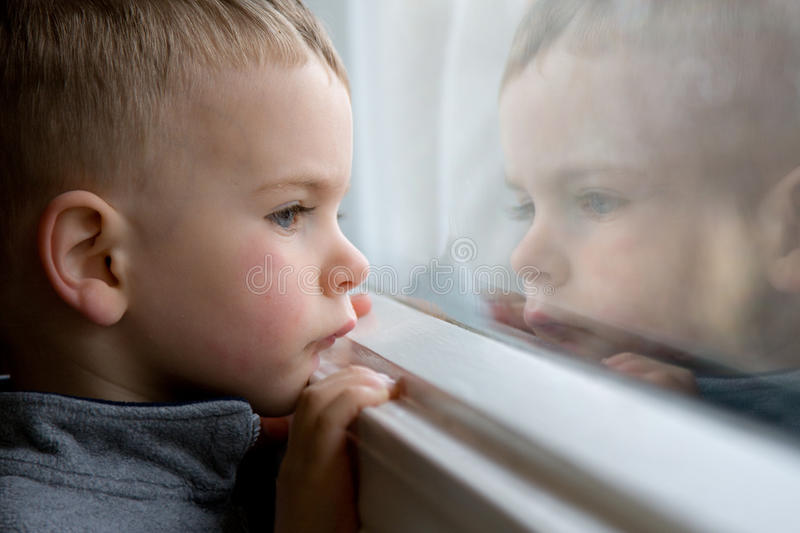 Boy looking out window royalty free stock photography